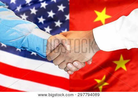 Business Handshake On The Background Of Two Flags. Men Handshake On The Background Of The American A
