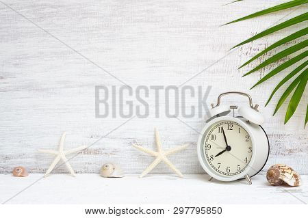 White Alarm Clock With Starfish, Sea Shells And Green Palm Leaf Background. Background Concept For S