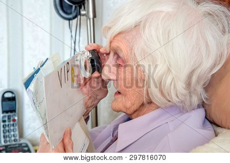 Visually Impaired Elderly Woman With Magnifying Loupe.