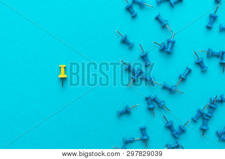 Yellow Push Pin Out Of The Crowd Concept Over Blue Backgound. Top View Of Think Different Concept