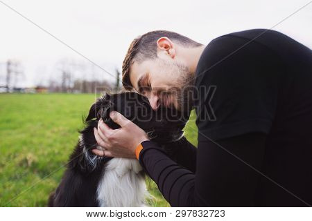Man Embracing His Border Collie Dog . Young Owner Hugs His Pet. Friendship Between Owner And Dog. An