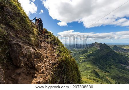 Two Persons Climbing Up The Trail To The Peak Of The Mountain Le Pouce On The Island Of Mauritius Wi