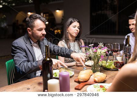 Hispanic Man Cutting Bread While Having Food With Pals In Backyard