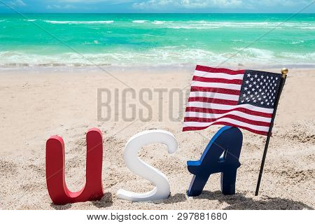 Patriotic Usa Background With Flag On The Sandy Beach Near Ocean