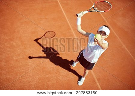 Female tennis player serving tennis ball