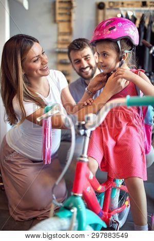 woman choosing new bicycle and helmet for happy little girl in bike shop