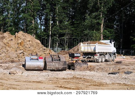 construction site with truck and dredger buckets with different blade configurations poster