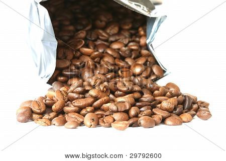 Whole coffee beans scattered and bag on white background