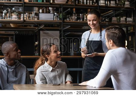 Diverse Friends Sitting In Restaurant Placing Order Talking With Waitress