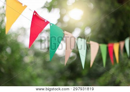 Garland Of Colorful Flags At Sunset In Summer Garden. Concept Of Celebration Happy Birthday Party. P