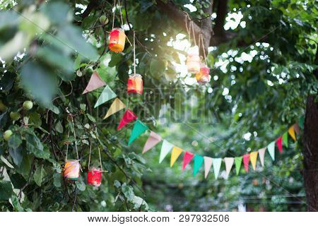 Garland Of Colorful Flags And Homemade Flashlights At Sunset In Summer Garden. Concept Of Celebratio