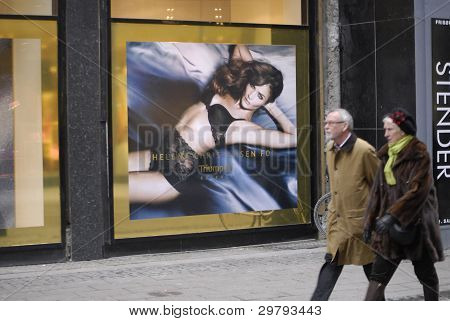 DENMARK / COPENHAGEN _ Senior couple pass by billboard with super model Helena Christensen model for Triumph essence hanging at Triumph store window at stroeget 8 February 2012 (Photo by Francis Dean/Dean Pictures)