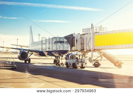 Big Modern Commercial Plane On Airfield Docked With Boarding Bridge At Sunrise Or Sunset. Blue Clear