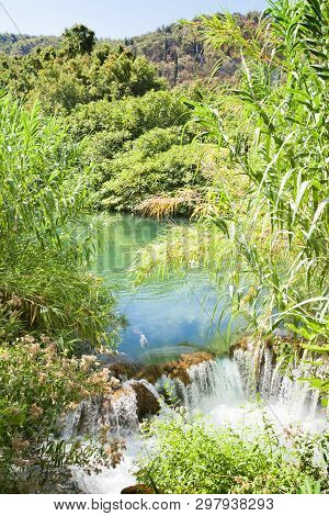 Krka, Sibenik, Croatia, Europe - Water Reed At A Small Waterfall Within Krka National Park