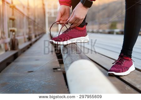 Running Shoes - Closeup Of Woman Tying Shoe Laces. Female Sport Fitness Runner Getting Ready For Jog