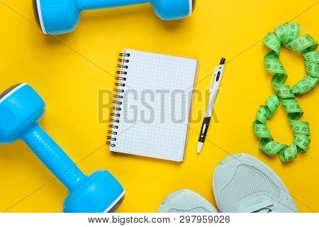 Fitness Concept, Workout Plan. Plastic Blue Dumbbells, Sport Shoes, Notepad, Ruler On A Yellow Backg