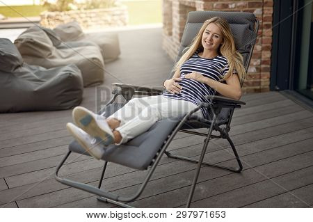 Happy Smiling Attractive Young Pregnant Young Woman Relaxing Outdoors On A Recliner Chair On A Woode