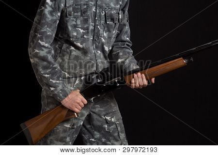 A Man With A Gun In Camouflage Military Uniform. Military Or Hunter With A Shotgun. Young Man Holdin