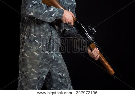 Soldier, Trooper On A Black Background. A Man With A Gun In Camouflage Military Uniform. Military Or