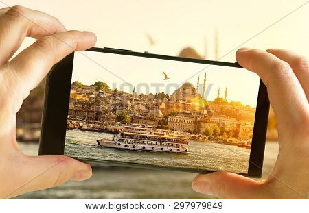Istanbul At Sunset, Turkey. Taking Photo Of Golden Horn By Cell Phone. Tourist Boat Sails In The Ist