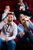 Couple and other people, probably friends, in cinema watching a movie; it seems to be a funny movie poster