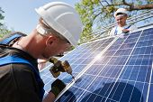 Technician connecting solar photo voltaic panel to metal platform using screwdriver on bright blue sky and shiny panel surface background. Stand-alone solar panel system installation concept. poster
