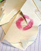 Broken relationship is illustrated with this torn envelope with lipstick smudge. Lipstick imprint is torn in half in emotional outrage over disillusionment with relationship gone sour. poster