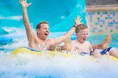 Thrilling expression of a father and his son as they splash down a water slide at an amusement park during a summer vacation. Lifestyle photo showing fun family activities poster
