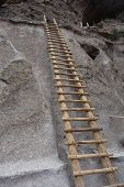 A sturdy ladder going up into the ancient cliff dwellings of Bandelier National Monument poster