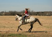 young cowgirl with hair flowing in the wind galloping her horse on a Texas ranch poster