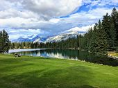A beautiful golf hole in the Jasper, Alberta, high in the Rockies mountains.  The fairway is beside a beautiful lake that reflects the surrounding forest in the water.Snowy mountains in the background poster