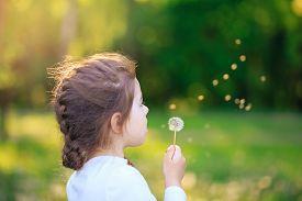 Cute Little Girl With Dandelion Flower Is Smiling In Spring Park. Happy Cute Kid Having Fun Outdoors