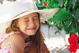 Beautiful Little Girl Looking At Red Flower And Smiling In Summer Park. Happy Cute Kid Playing Outdo
