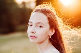 Portrait Of Beautiful Serious Teen Girl Is Enjoying Nature In The Park At Summer Sunset