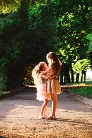 Two Cute Little Girls Hugging And Laughing At The Garden At Warm Summer Evening. Happy Kids Outdoors