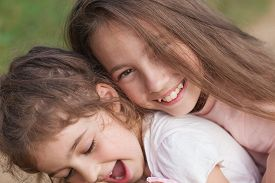 Portrait Of Two Happy Little Girls Laughing And Hugging At The Summer Park. Happy Childhood Concept