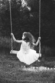 Black And White Portrait Of Cute Little Girl Smiling On Swing At Summer Day, Happy Childhood Concept