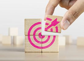 Hand Putting The Last Piece Of Wooden Blocks With The Dart Target Icon. Goal, Business Goal, Achievi