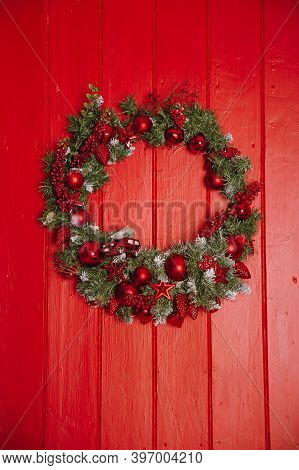 Christmas Wreath Of Pine Branches With Candles On A Red Wooden Background, Christmas Balls, Copy Spa