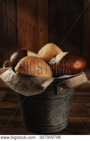 Closeup of a bucket filled with dinner rolls with warm side light. Vertical format with copy space.