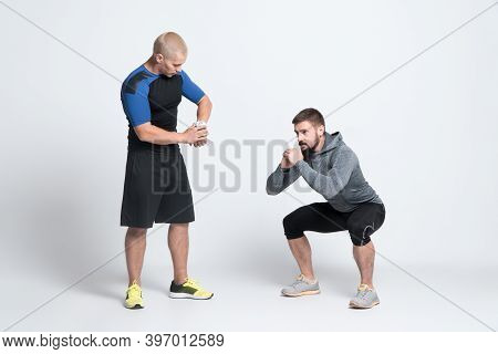 Sport Man Exercising With Personal Fitness Trainer On White Background