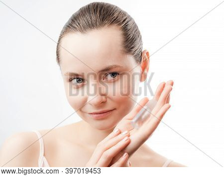 Beautiful Young Woman With Clean Fresh Skin Showing The Product For Skin Care. Girl Beauty Face Care
