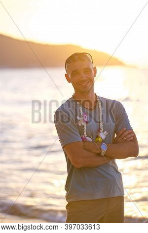 Vertical Photo, A Man With A Flower Garland On His Neck On The Seashore In The Rays Of The Sun, A Be