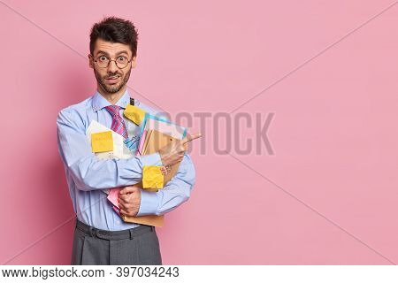 Puzzled Displeased Male Economist Dressed In Formal Outfit Holds Folders And Has Stickers Stuck To S