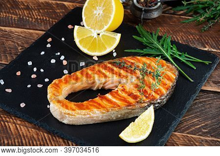 Grilled Salmon Fish On Stone Board. Salt Atlantic Salmon Fried On Grill With Lemon