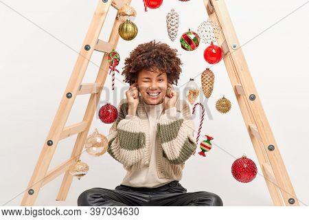 Pleased Dark Skinned Woman Plugs Ears As Hears Loud Sound Clenches Teeth And Winks Eyes Sits On Floo