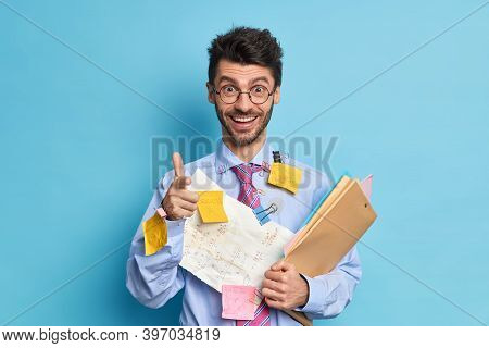 Cheerful Young Man Coworker Happy To Finish Project Work Covered With Papers And Stickers Points At