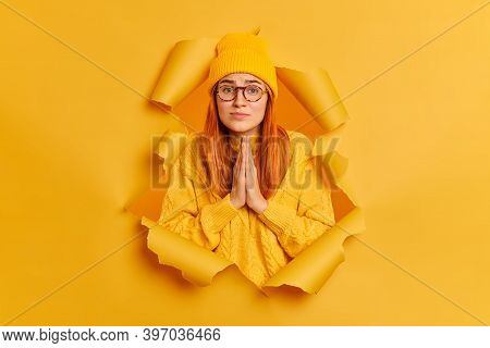 Hopleless Sad Woman Has Imploring Expression Keeps Palms Together Asks For Apology Wears Yellow Hat