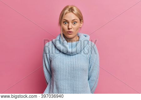 Beautiful Surprised Blonde Woman Keeps Eyes Widely Opened Stands Startled Indoor Wears Knitted Sweat