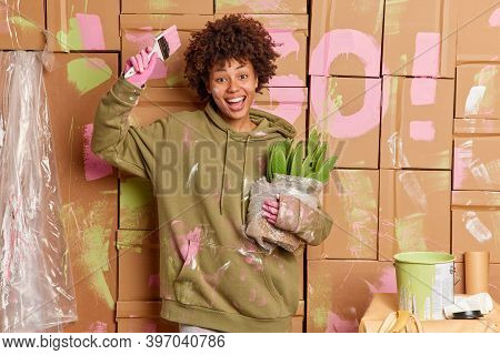 Joyful Dark Skinned Woman Painter Renovates New House Moves In Apartment Paints Walls Holds Paintbru